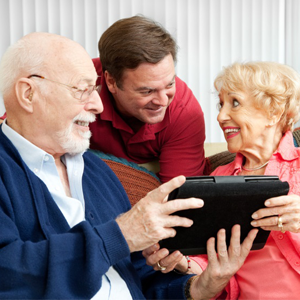Older Parents and Son Looking At Tablet